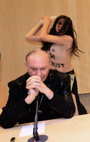 An activist from women's rights group Femen sprays water at Belgian Archbishop of Mechelen-Brussels and Primate of Belgium Leonard during a conference at Brussels university ULB